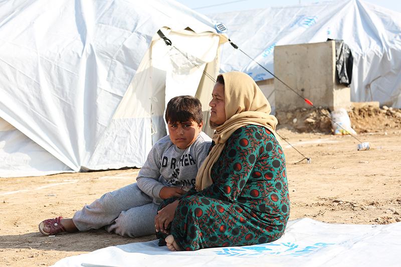 텐트 밖에 안자 있는 어머니 자밀라 씨와 아들 모하매드