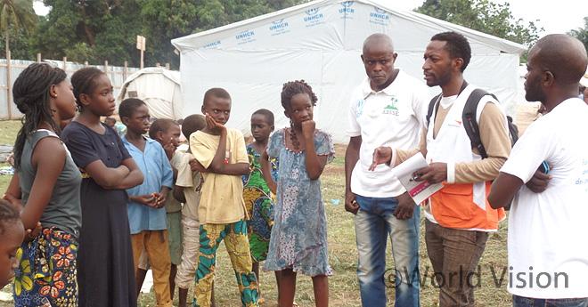 월드비전 직원이 중앙아프리카 출신 난민들과 이야기를 나누고 있는 모습,  콩고민주공화국에 위치한 난민캠프 (출처:월드비전)