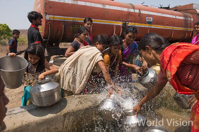 정부가 제공한 물탱크에서 물을 긷는 주민들(사진출처:월드비전)