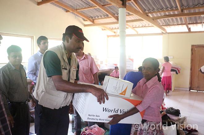 월드비전 직원과 구호물품을 전달받는 스리랑카 주민