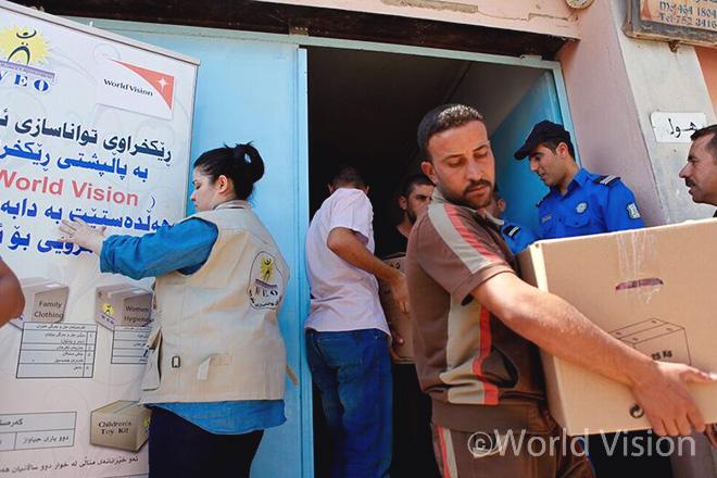이라크 도훅(Dohuk) 난민 캠프에서 사람들에게 구호 물품을 나눠주는 모습 (출처: 월드비전)