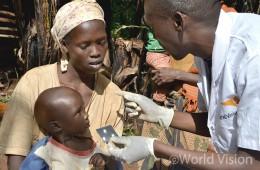 말라리아를 앓고 있는 아이 디빈(Divin)은 엄마와 함께 진단을 받고 치료약에 대한 설명을 듣고 있습니다 (사진출처: 월드비전)