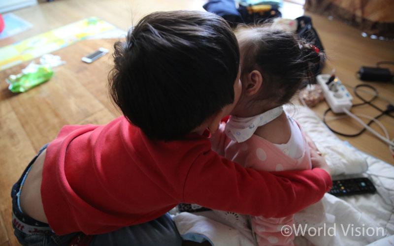 아픈 동생을 안아주는 오빠 호진이. 호진이는 올해 학교에 들어갔지만 학습지 하나, 학원 하나 다니는 게 없다.