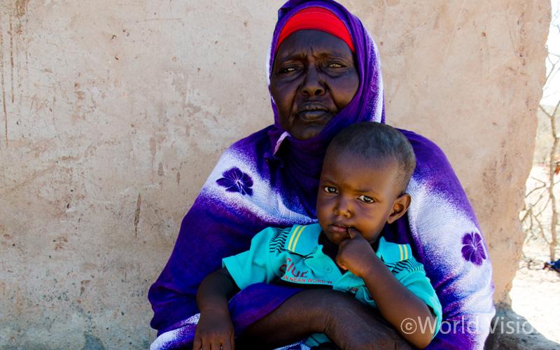 손자와 함께 그늘에서 햇빛을 피하고 있는 파두마 할머니 (출처: 월드비전)