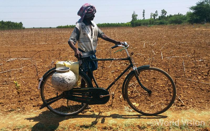 가뭄으로 말라붙은 경작지를 우두커니 바라보고 서있는 농부의 모습 - 안드라 프라데시 주(州) 칸두쿠르 지역 (출처: 월드비전)