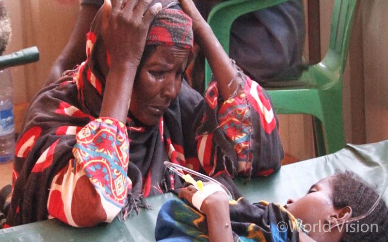 콜레라에 걸려 병원 치료를 받고 있는 손녀 마리암(Mariam)의 모습에 눈물 짓고 있는 할머니 – 바이도아/소말리아 (출처: 월드비전)
