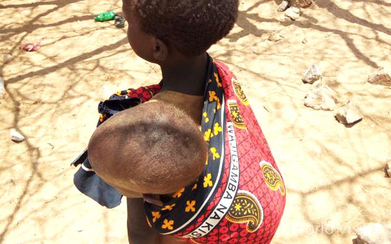 어린 동생을 등에 업은 채 점심 시간이 되기만 기다리고 있습니다 - 투르카나/케냐 (출처: 월드비전)