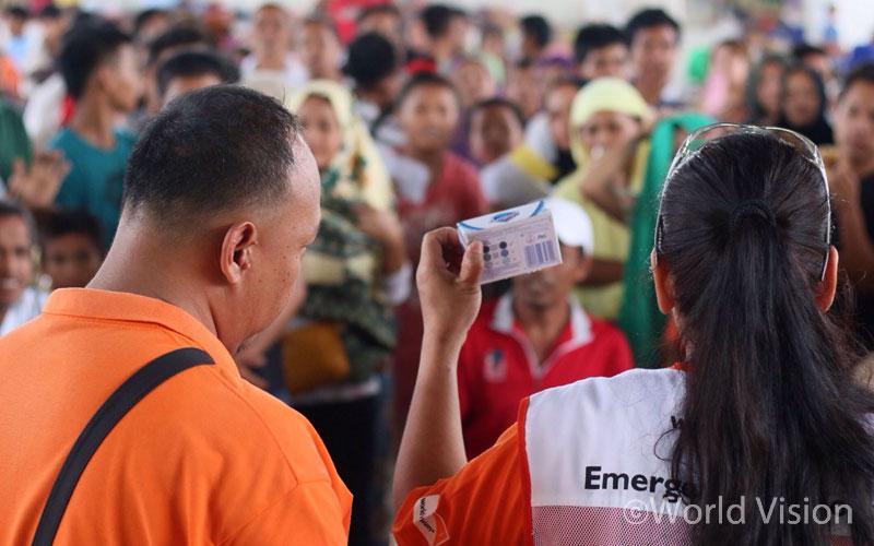월드비전 직원이 임시 피난처에 모인 피난민들에게 구호물자를 나눠주며 각각의 물품 사용법을 안내해주고 있습니다(출처:월드비전)