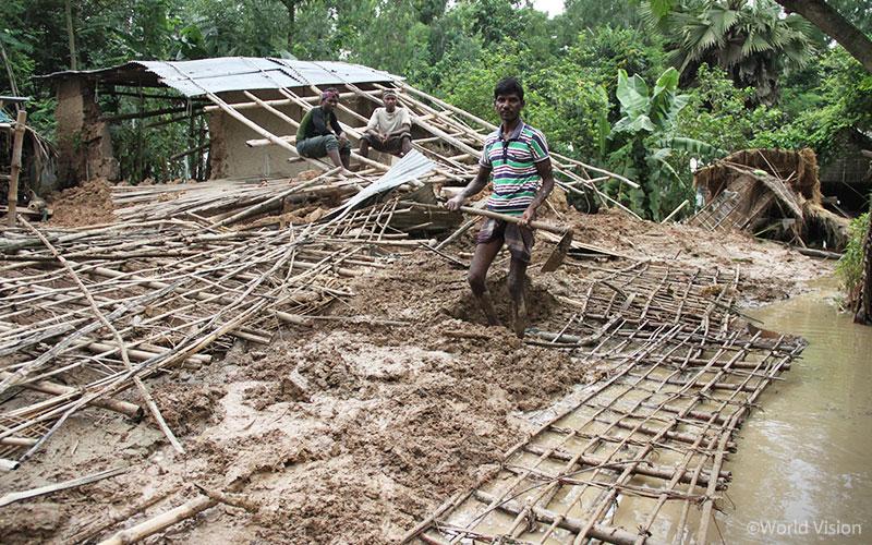 홍수가 지나간 이후 폭삭 내려 앉은 집의 모습, 집터에 한 가득 쌓여 있는 진흙 더미를 치우고 있습니다. (출처: 월드비전)