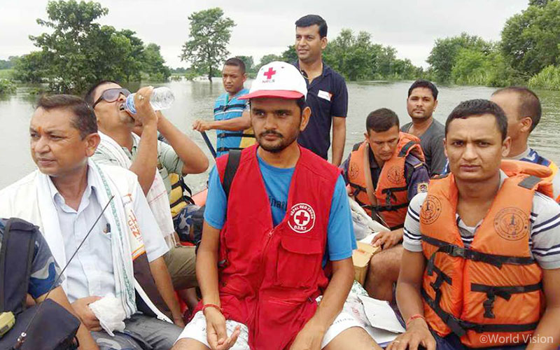 네팔 월드비전 직원들이 보트를 타고 불어난 강물을 건너, 주민들에게 구호 물품을 전달하고 있습니다. (출처: 네팔 월드비전)