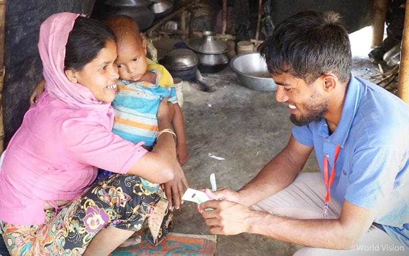 아이의 영양실조 상태를 검사하고 있는 월드비전 직원(출처:월드비전)