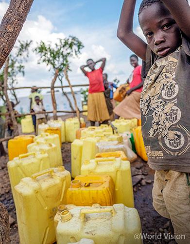 임베피 난민촌에 설치된 식수 펌프를 사용하는 아동의 모습 (사진출처: 월드비전)