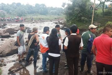 ▲ 화산 폭발로 피해를 입은 마을의 모습을 바라보는 주민들과 월드비전 직원(출처: 월드비전)