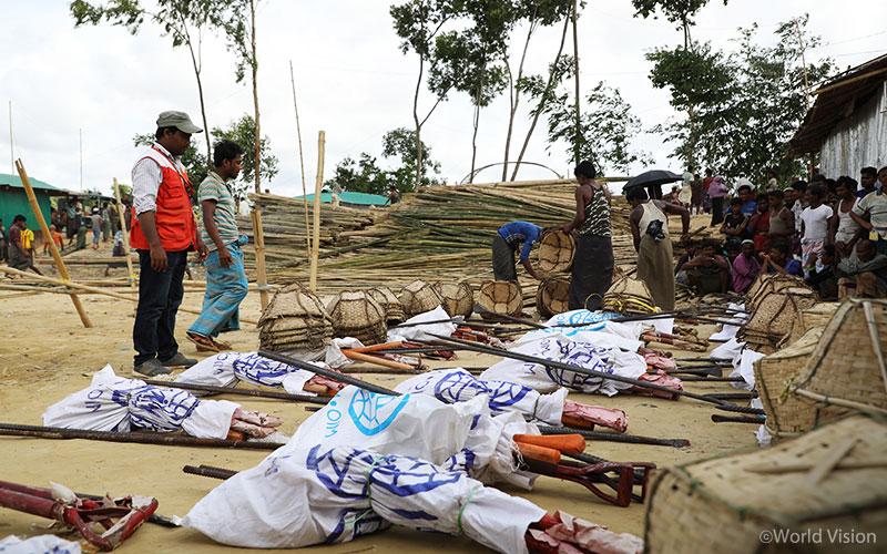 ▲ 삽, 대나무, 천막 등으로 만들어진 수리 키트를 난민들에게 나눠주고 있는 모습(출처: 월드비전)