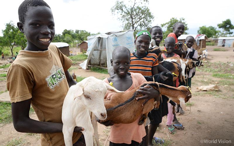 월드비전 생계지원사업을 통해 지원받은 염소를 안고 기뻐하는 아이들의 모습(출처: 월드비전)