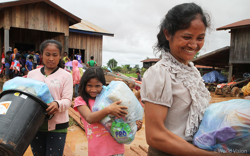 ▲ 위생키트를 받고 기뻐하는 라오스 주민과 아이의 모습 (출처: 월드비전)