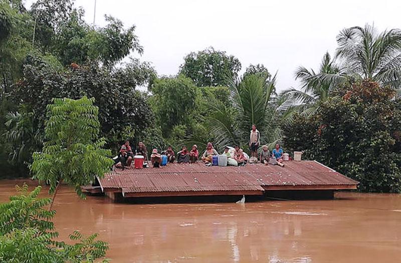 ▲갑작스러운 홍수에 대비하지 못해 지붕 위에 위태롭게 피신해 있는 피해 마을 주민들의 모습(출처:CBS)