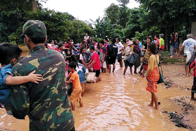 ▲라오스 정부군의 도움을 받아 대피하고 있는 피해 마을 주민들의 모습(출처:Reuters)