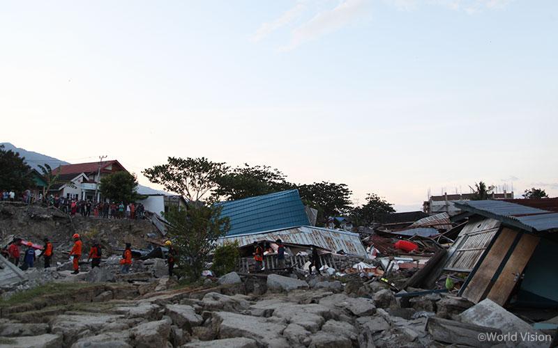 지진과 쓰나미로 무너진 콘크리트 벽과 지붕 사이로 구조 작업이 진행되고 있습니다. (출처: 월드비전)