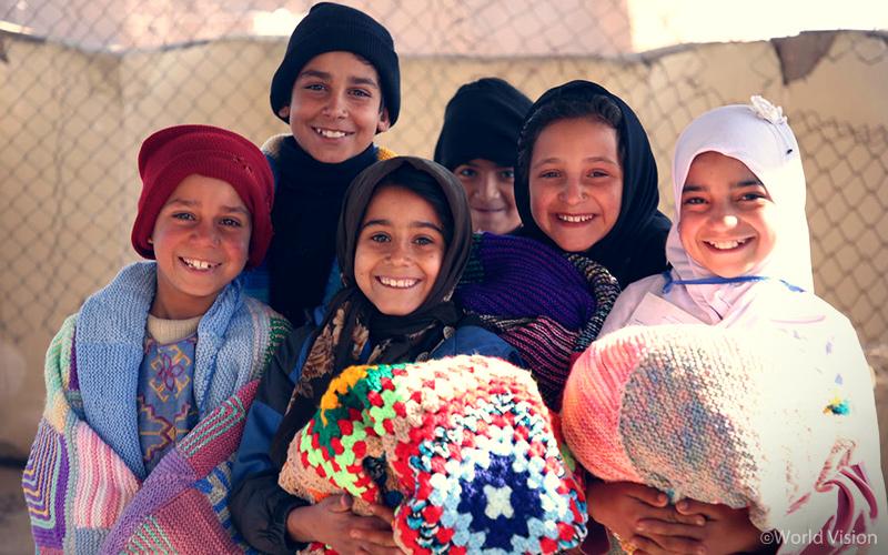 담요를 배급 받고 좋아하는 아프가니스탄 헤라트 거리아동센터 아이들(월드비전)