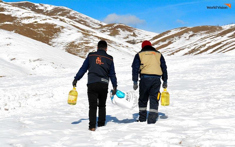 코로나19로 인해 생계의 위협을 받고 있는 취약계층에게 식량을 배송하고 있는 몽골 월드비전 직원들.눈밭을 걷고 있는 모습.