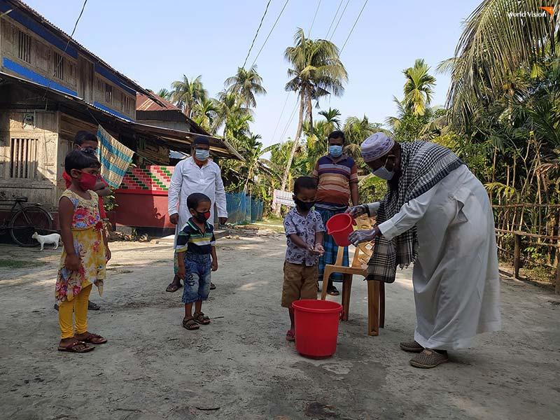 방글라데시 종교지도자가 지역 아동들에게 올바른 손 씻기 방법을 가르치고 있다