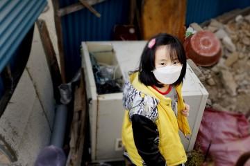 쓰레기 가득한 집안에 서있는 여자아이