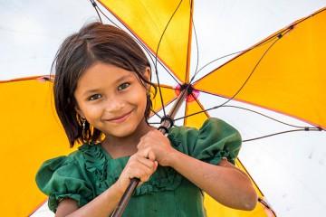 여자아이가 월드비전 우산을 들고 웃는 모습