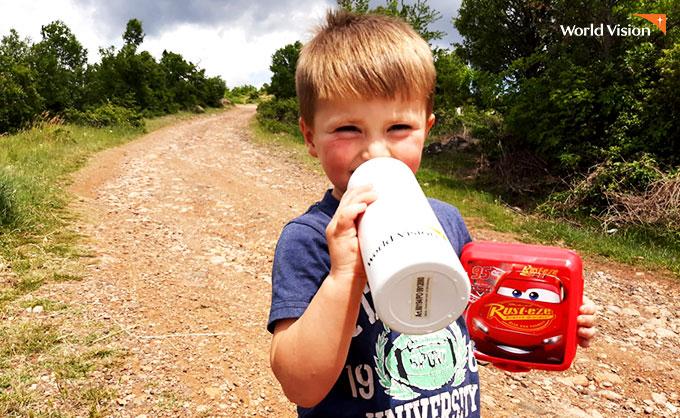 도시락통과 물병 선물을 받고 즐거워하는 아이. 사진