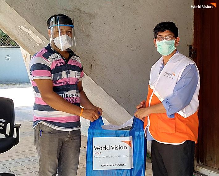 월드비전 직원이 관계자에게 마스크를 전달하는 모습