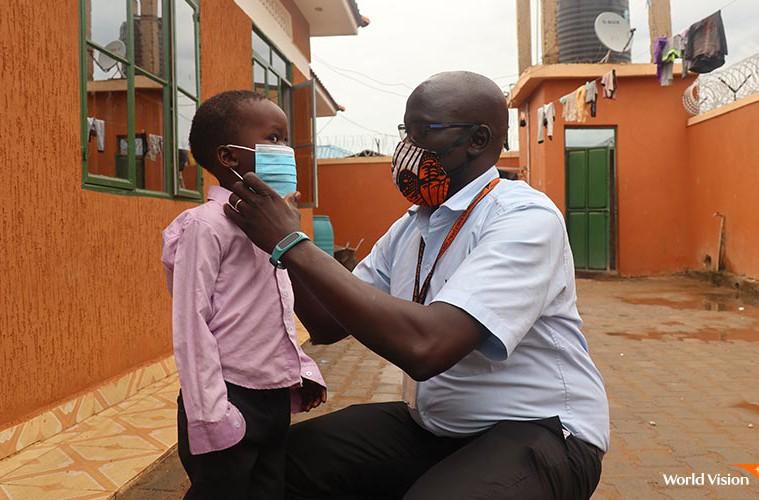 월드비전 직원이 아동에게 마스크를 착용시키는 모습