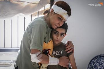 폭팔사고로 머리와 팔을 다친 엄마가 아이를 안고있는 두려움에 떨고 있는 모습