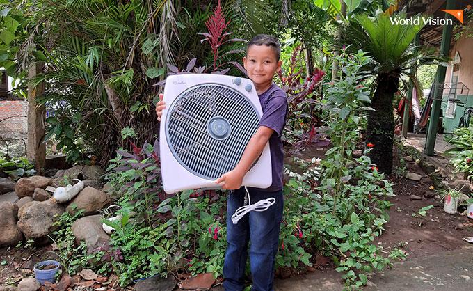 선풍기를 받고 즐거워하는 아이. 사진