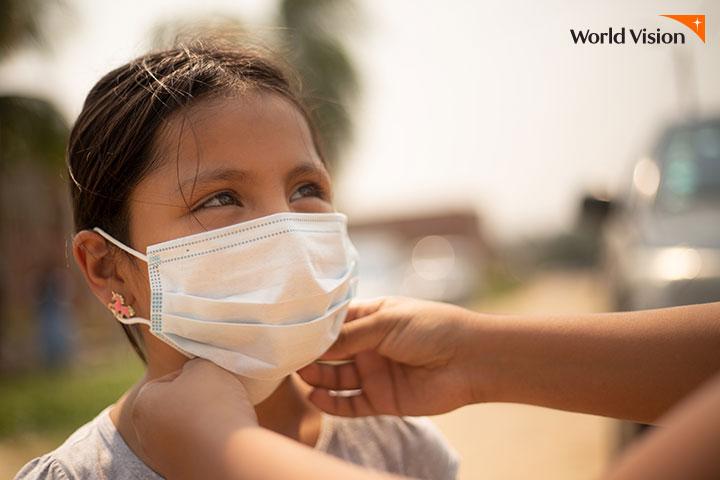 월드비전 직원이 씌워주는 마스크를 차고 있는 여자 어린이의 얼굴