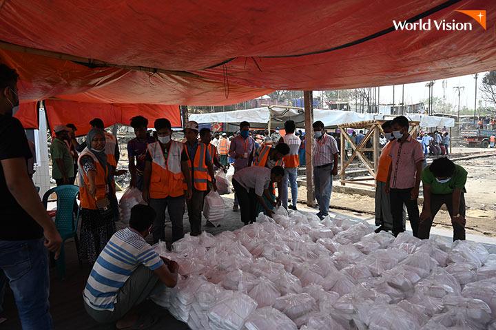 월드비전 직원들이 주민들에게 식량을 나눠주고 있는 모습