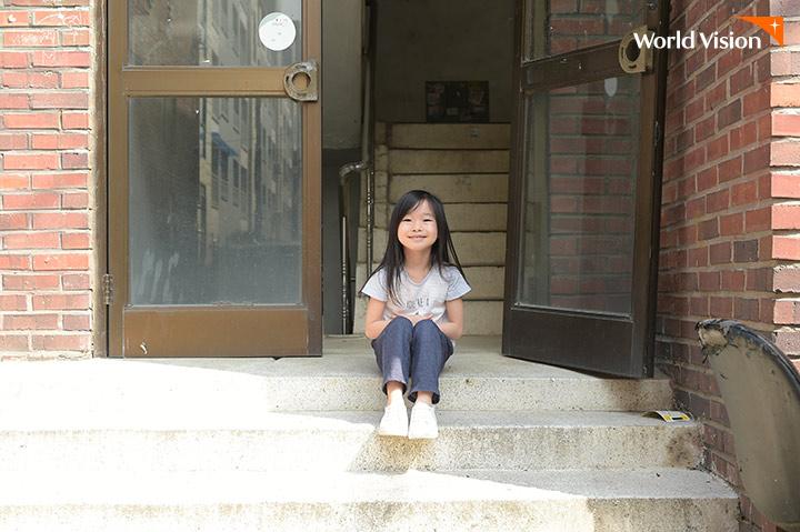 낡은 빌라 입구에 앉있는 여자아이의 모습