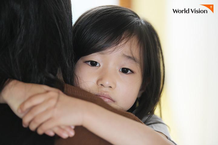 어른의 품에 안기어 무서워하는 표정을 짓고 있는 여자아이