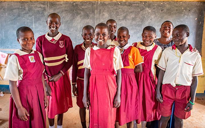 교실 칠판 앞에 서있는 교복을 입고 탄자니아 여학생들